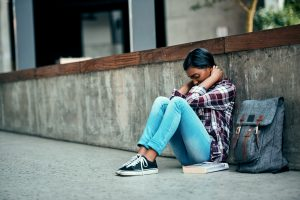 Shot of a young female student sitting on the floor feeling depressed outside on campus